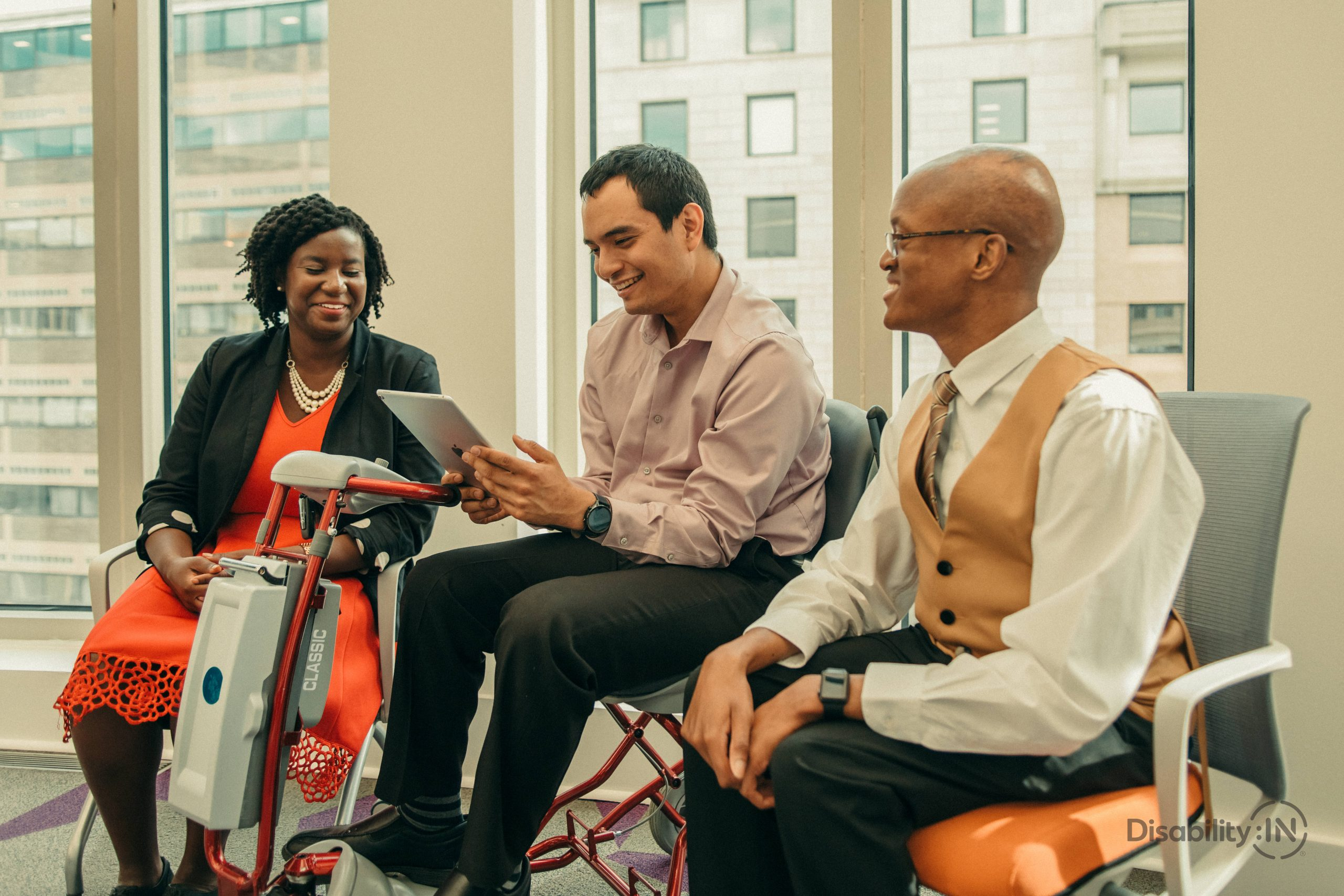 A group of 3 professionals gathered around a piece of assistive technology.