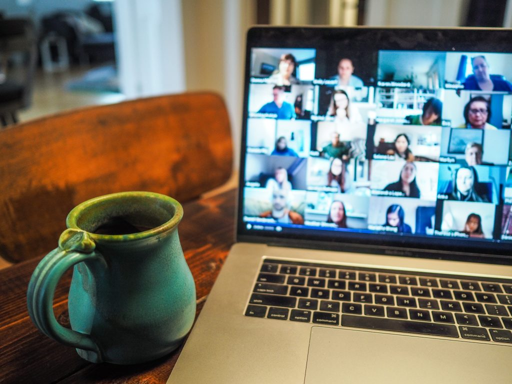 Image of a laptop computer with multiple diverse individuals on a video conference call.